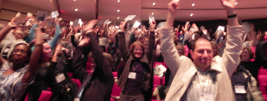 People with hands in air during conference